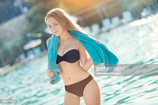 Blonde Teenage Girl with Towel by the Swimming Pool