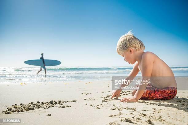 Blonde Three Year Old Boy Lying On The Beach