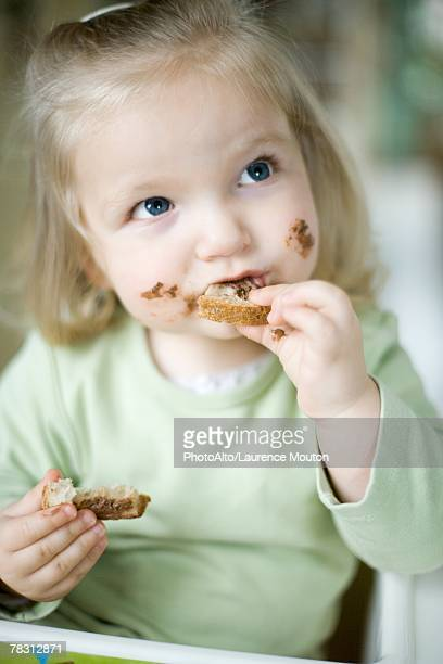 Blonde toddler girl eating bread with chocolate