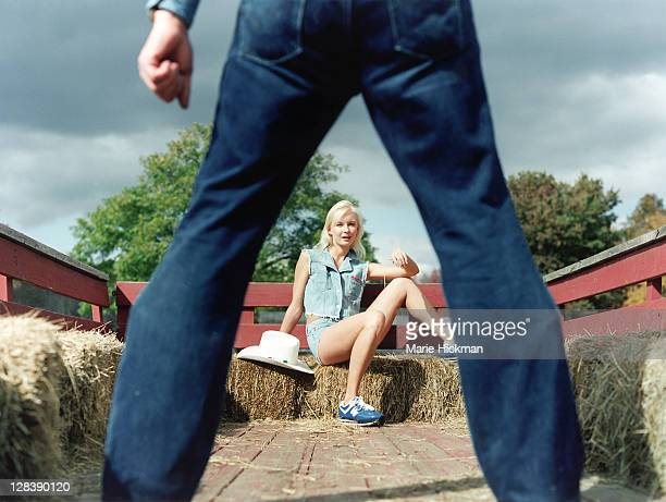 Blonde woman, 24 years old, sitting on haybales facing a pair of man's legs in jeans, Sherwood Farms in Easton, Connecticut