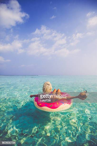Blonde woman chilling and floating on inflatable doughnut in ocean, Maldives