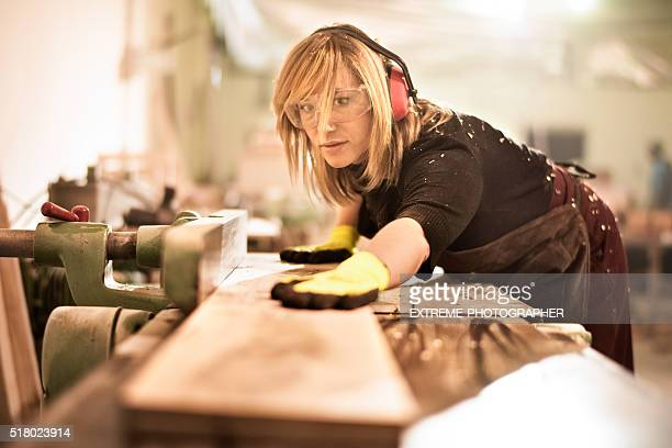 Blonde woman cutting planks