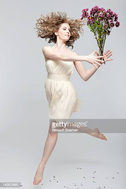 Blonde woman dancer in dress with purple daisies
