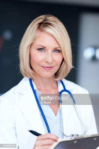 Blonde Frau Arzt mit Zwischenablage im Büro