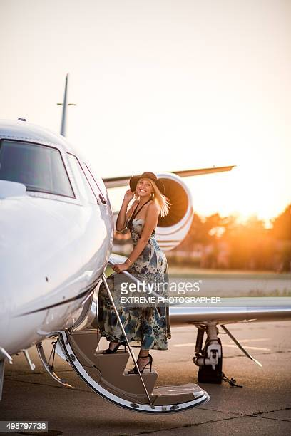 Blonde woman entering private jet airplane