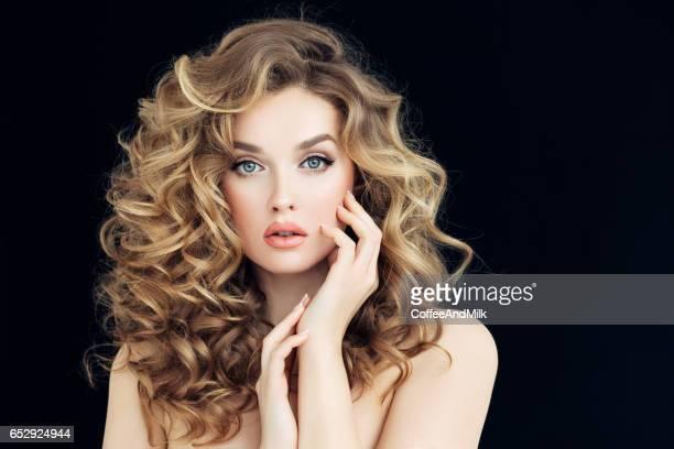 Blonde woman fashion model posing against black background