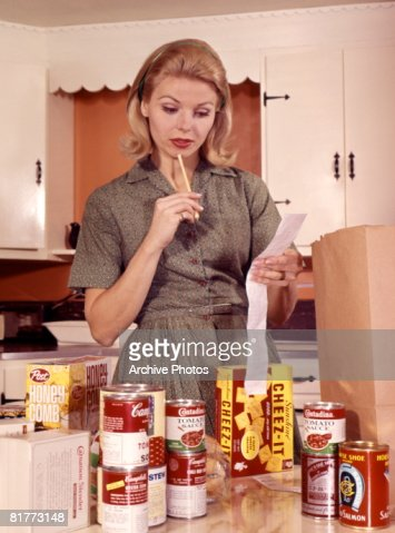 Blonde Woman Housewife In Kitchen Compare Cash Register Receipt To Items Groceries On Counter Brown Shopping Bag. : Stock Photo