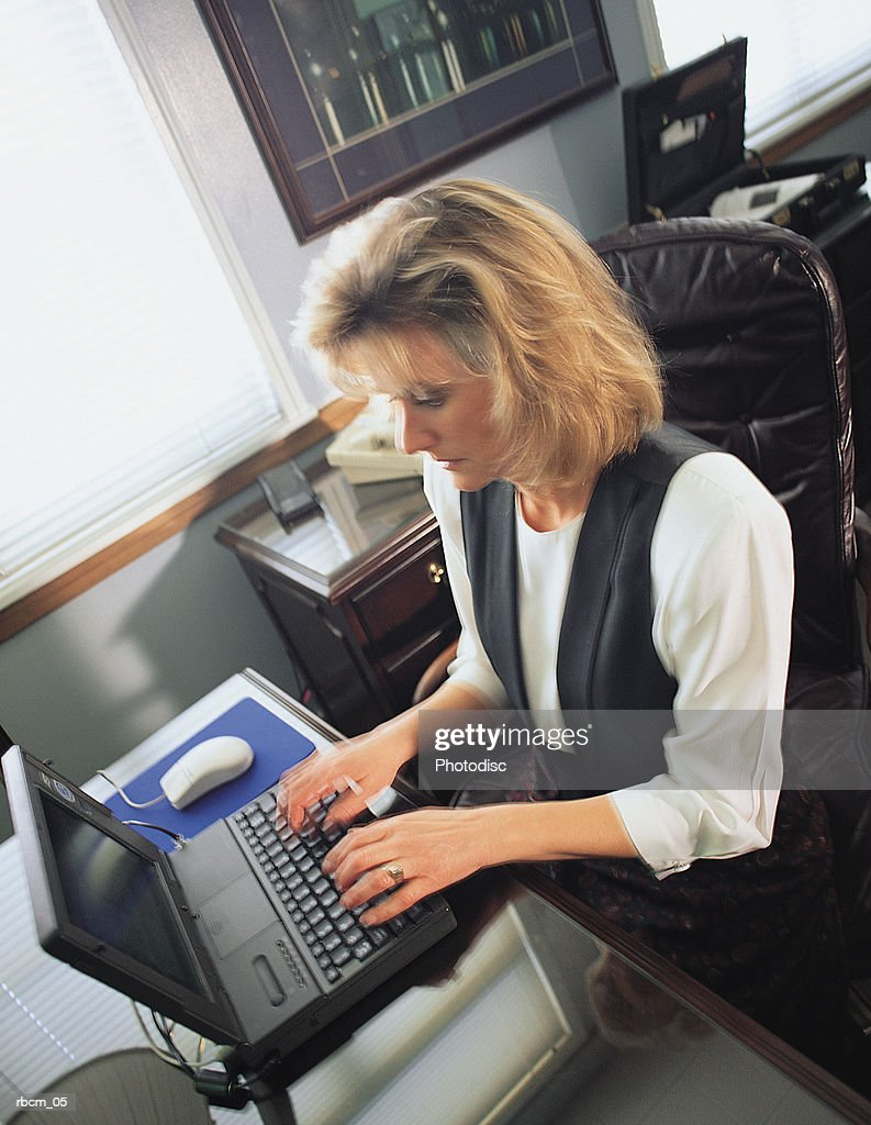 A blonde woman in a white shirt and black vest sits at a desk while typing on a laptop computer in an office : Stock Photo