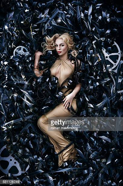 Blonde woman is lying on film reels