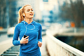 Young blonde woman is jogging on the bridge early in the morning.