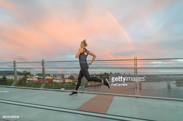Blonde woman jogging on bridge listening to music