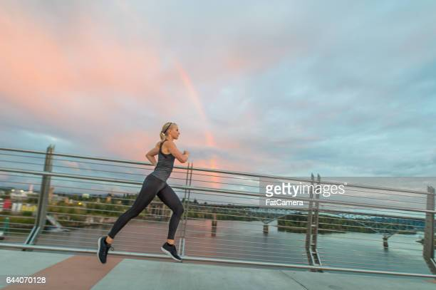 Blonde woman jogging on bridge
