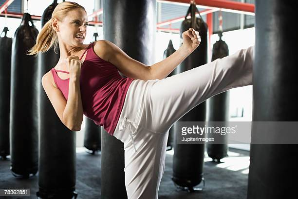 Blonde woman kicking punching bag