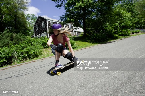 A blonde woman longboards down a New England road.