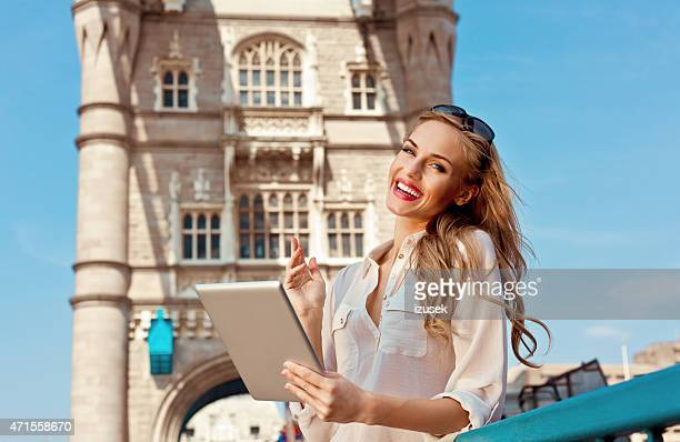 Blonde woman on Tower Bridge in London holding digital tablet