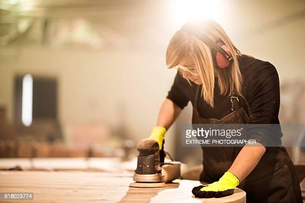 Blondine Frau macht abgeschmirgelten Holzmöbeln