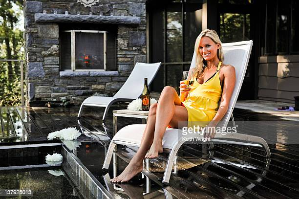 Blonde woman relaxing by spa pool.