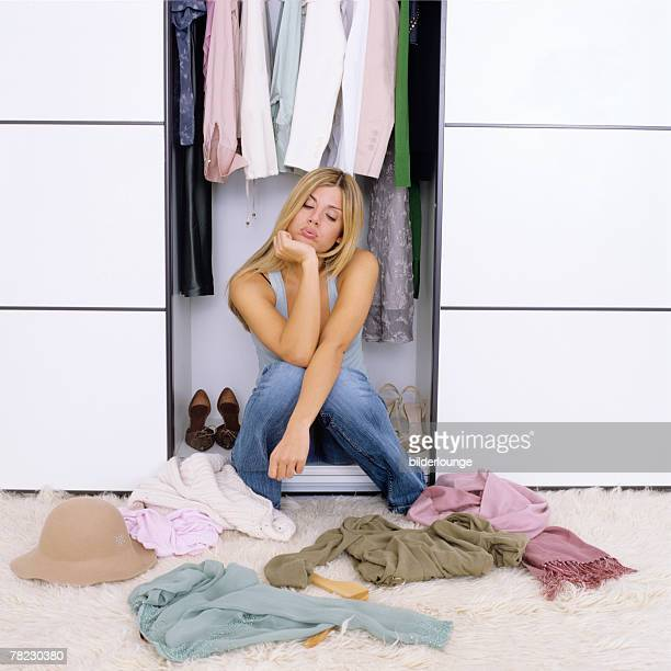 blonde woman sitting in wardrobe and looking frustrated