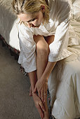 blonde woman sitting on bed wearing white nightgown feeling newly shaven legs