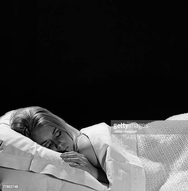 A blonde woman sleeping in bed underneath a blanket circa 1960