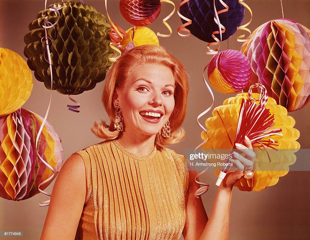 Blonde woman smiling surrounded by confetti, balloons and party decorations. (Photo by H. Armstrong Roberts/Retrofile/Getty Images) : Stock Photo