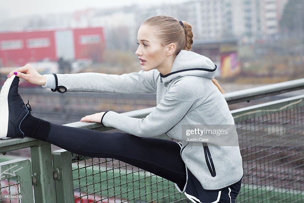 blonde woman stretching her leg in urban scene : Stock Photo