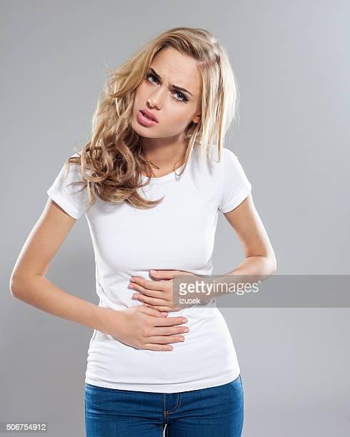 Blonde Frau unter Bauchweh