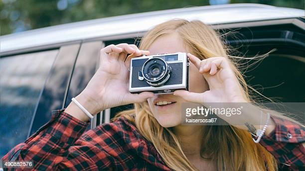 Mulher loura a foto do carro com uma antiga câmara