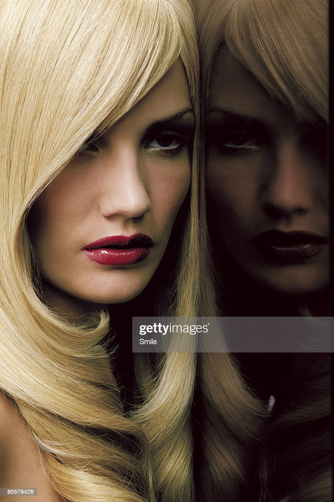 Blonde woman with dark reflection in glass : Stock Photo