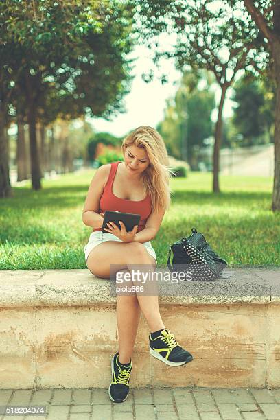 Blonde woman with digital tablet at park
