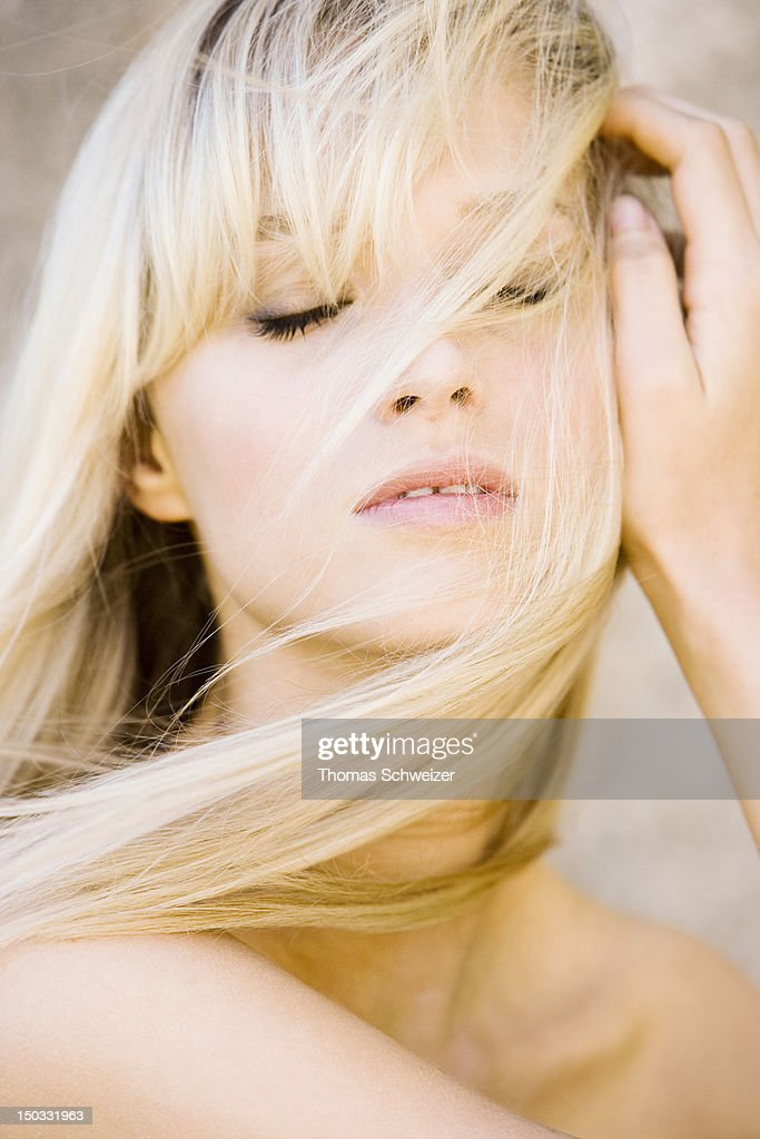 A blonde woman with hair falling across her face : Stock Photo