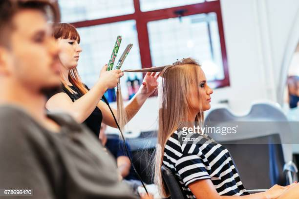 Blonde woman with long hair at hair stylist, having her hair washed and cut