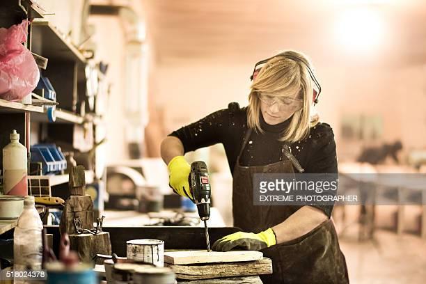 Blondine Frau arbeitet mit elektrischen Bohrmaschine
