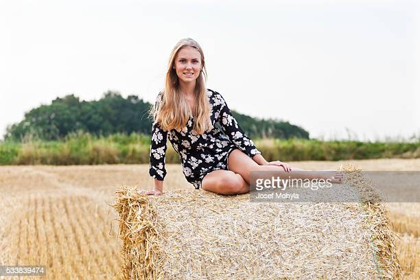 Blonde young woman sitting on straw ball