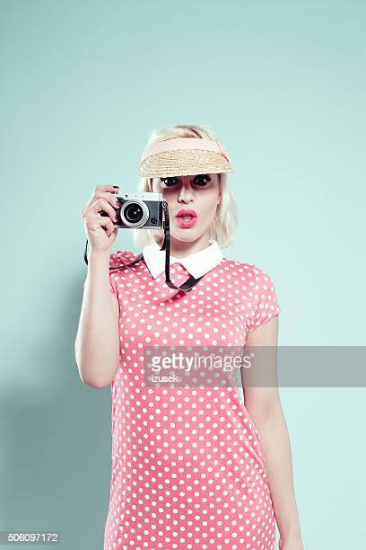 Blonde young woman wearing sunshade cap, holding camera