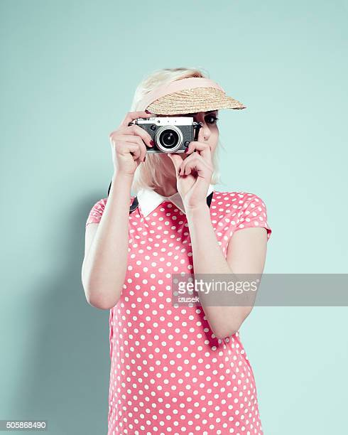 Blonde young woman wearing sunshade cap, photographing