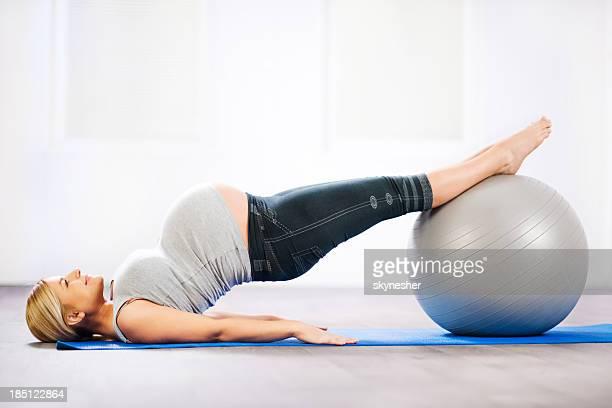 Blondie femme enceinte faisant exercice.