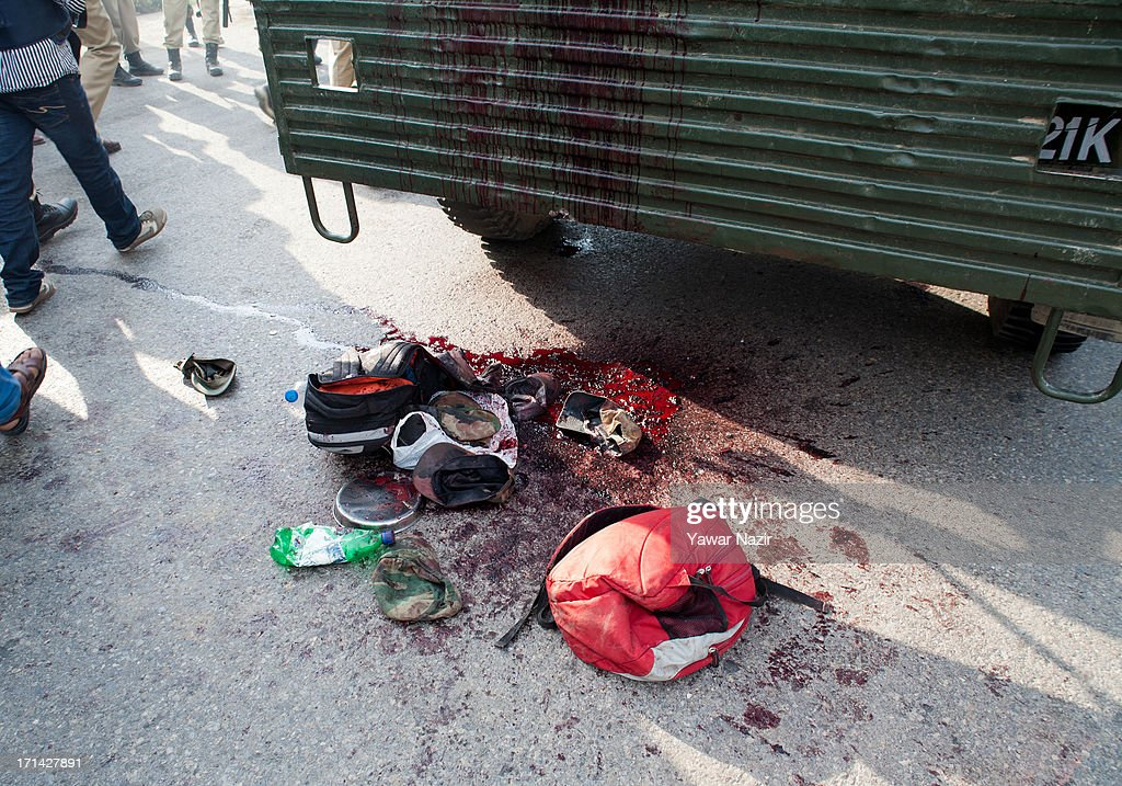 Blood and belongings of killed Indian army soldiers lie scattered on a road after their vehicle was attacked by militants on June 24, 2013 in Srinagar, the summer capital of Indian administered Kashmir, India. Suspected militants opened fire on an Indian army convoy on the outskirts of Srinagar, killing at least five and wounding seven others, ahead of Indian Prime Minister Manmohan Singh's visit to the disputed Himalayan region tomorrow. The militants fled from the scene and half an hour later hurled a grenade on Indian paramilitary forces in Barzulla area , some two kilometers away. Hizbul-Mujahideen, the largest guerrilla group fighting Indian rule since 1989, claimed responsibility for today's attack, and had just two days before gunned down two policemen in the heart of Srinagar city.