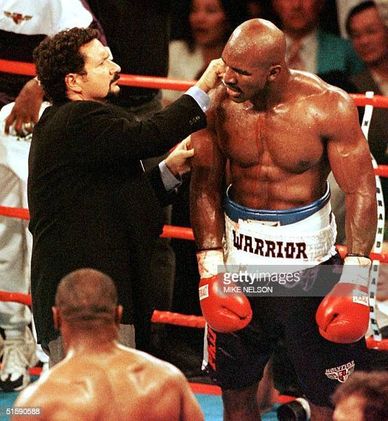Blood flows down his arm and chest as Evander Holyfield has his ear examined by the ringside doctor 28 June 1997 during his WBA heavyweight...