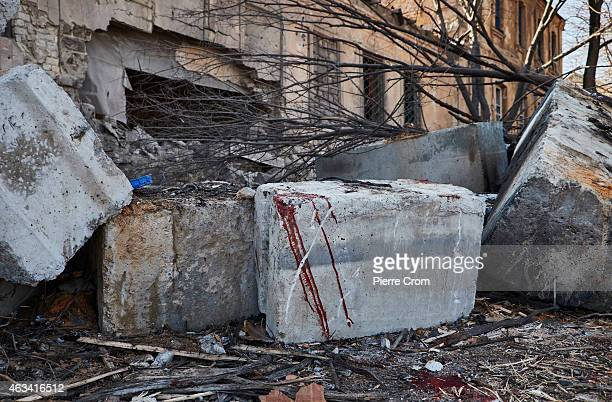 Blood from a Cossack DPR fighter who was killed on the roadblock is seen on rubble in the streets as fighting continues in the area on February 14...
