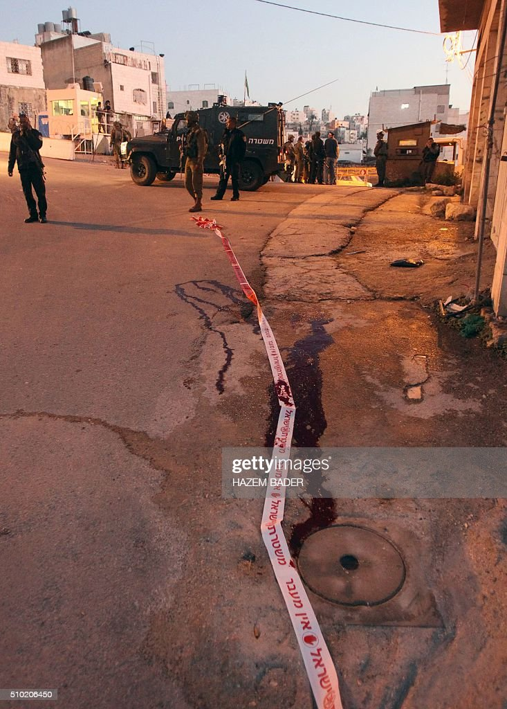 Blood is seen on the ground as Israeli security forces gather at the site of a stabbing attack near the shared religious site known to Jews as the Cave of the Patriarchs and to Muslims as the Ibrahimi Mosque, in the West Bank town of Hebron, on February 14, 2016. A female Palestinian tried to stab an Israeli policeman in the West Bank city of Hebron but was shot and critically wounded, police said, in today's third violent incident. BADER