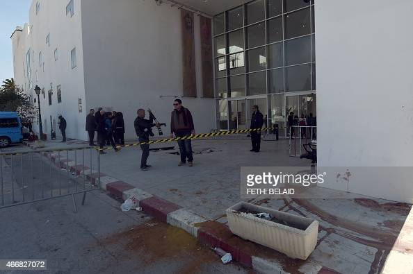 Blood stains the ground as journalists and security forces stand at the visitors entrance of the National Bardo Museum in Tunis on March 19 in the...