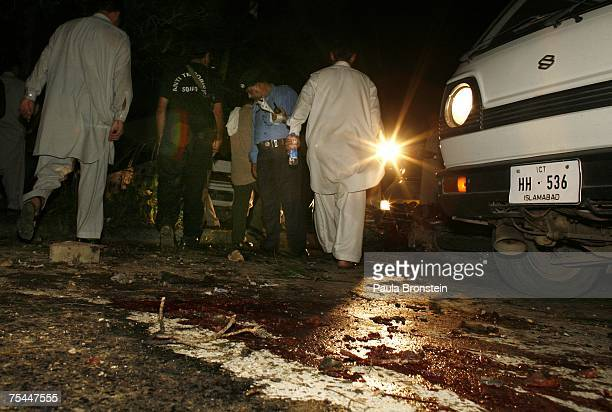 Blood stains the street as Pakistani officials look for evidence at a the site of a bomb blast where the former Chief Justice Iftikhar Chaudhry was...