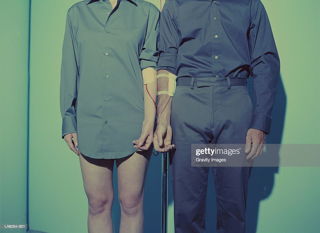 Blood transfusion, couple standing in front of blood bag, mid section : Stock Photo
