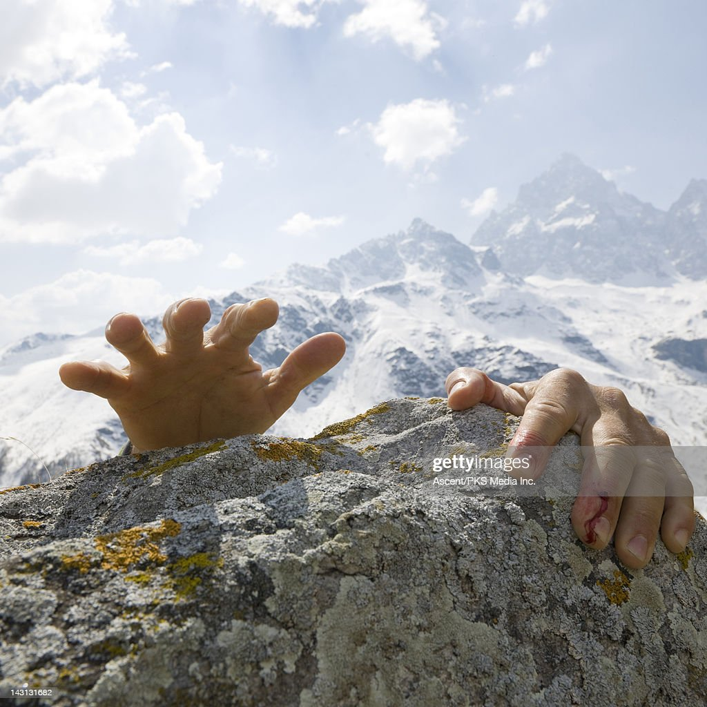 Bloodied climber's hands reach for summit rocks : Stock Photo