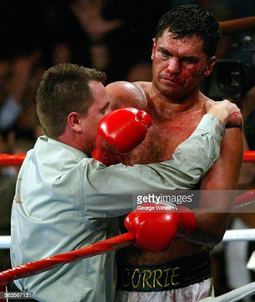 4/24/2004 – A bloodied Corrie Sanders is lead back to his corner by referee Jon Schorle after ref stopped the fight in the 8th round and awarded a...
