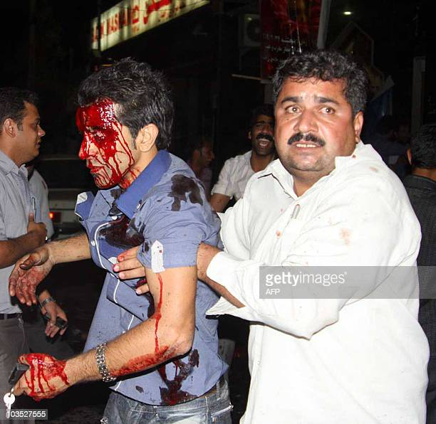 A bloodied victim is tended to outside the Jameh mosque in the southeastern Iranian city of Zahedan on July 15 2010 Two suicide bombings at a Shiite...