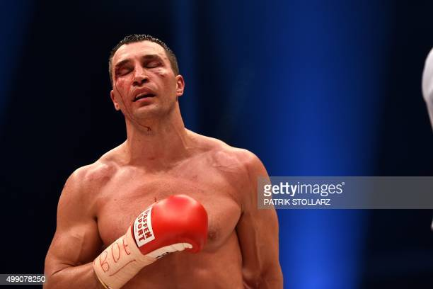 A bloodied world heavyweight boxing champion Wladimir Klitschko of Ukraine returns to his corner between rounds against Britain's Tyson Fury during...
