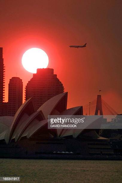 A bloodred sun coloured by bushfires west of the city sets over the Sydney Opera house 03 January 2002 In the tenth consecutive day of regional...