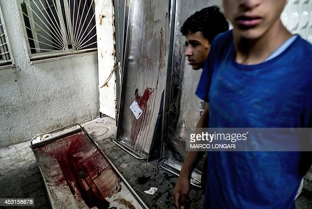 Bloodstained gurneys are seen outside the morgue at the Kamal Adwan hospital in Beit Lahia as members of the Abu Nejim family gather to collect their...